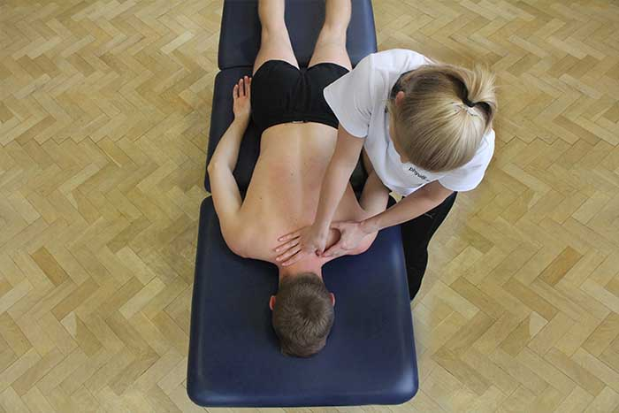 Customer receiving shoulder massage in relaxed position in Manchester Physio Clinic