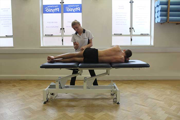 Customer receiving thigh massage while laying on his side in Manchester Physio Clinic