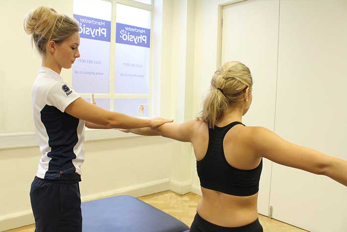 Customer reciving arm massage, while stretching in Manchester Physio Clinic