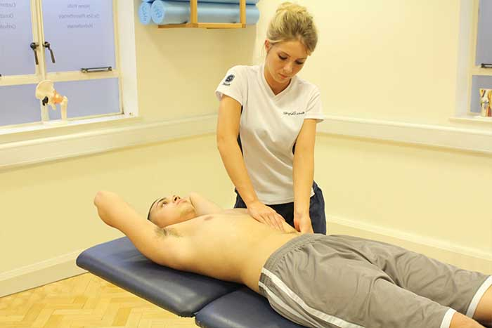 Customer receiving abdominal massage while in a relaxed position