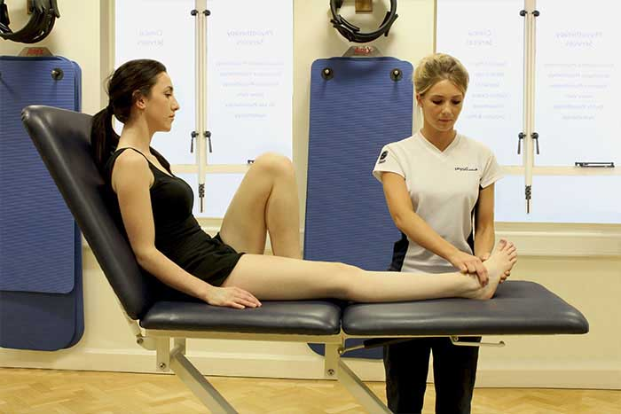 Customer receiving foot massage while in a sitting up position in Manchester Physio Clinic
