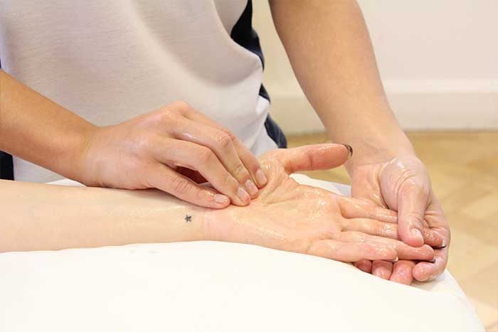 Customer reciving hand massage while in a relaxed position in Manchester Physio Clinic