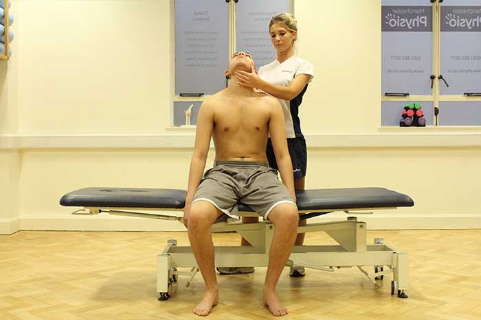 Customer receiving a jaw stretch while in a sitting position in Manchester Physio Clinic