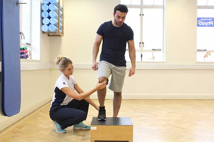 Customer guided through leg treatment by instructor in Manchester Physio Clinic