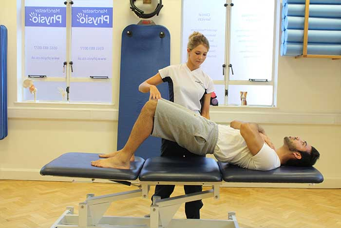 Customer increasing flexibility Customer maintaining back stretches in Manchester Physio Clinic in Manchester Physio Clinic