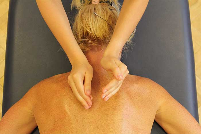 Customer receiving an upper back massage while in a relaxed position in Manchester Physio Clinic