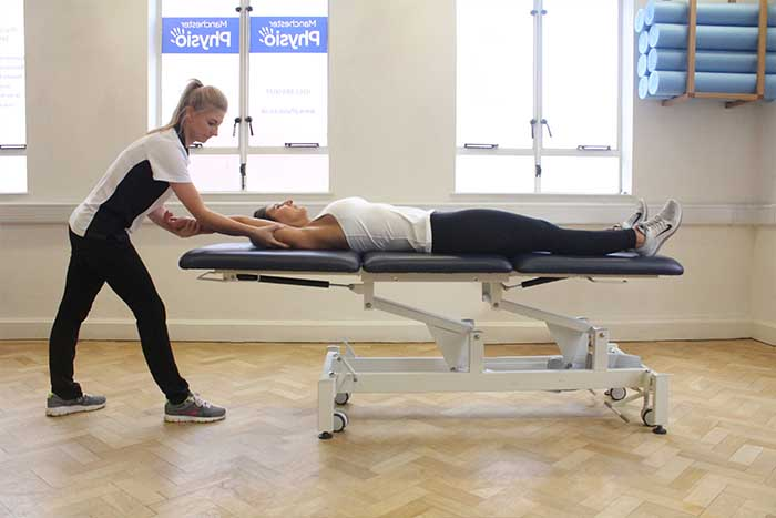 Customer receiving an arm stretch while in a relaxed position in Manchester Physio Clinic