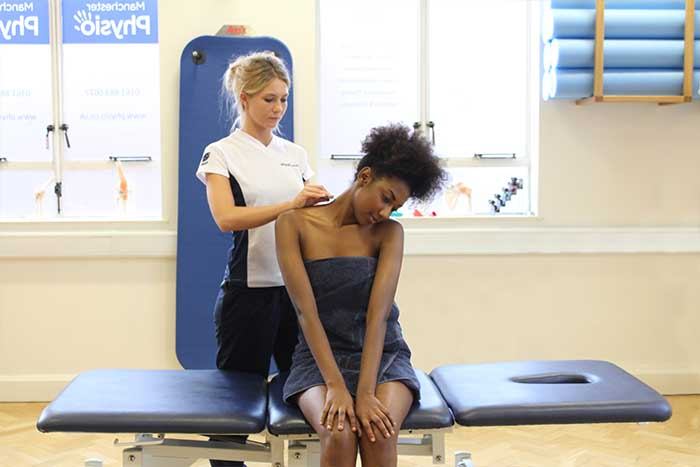 Customer receiving a shoulder massage while in a sitting position
