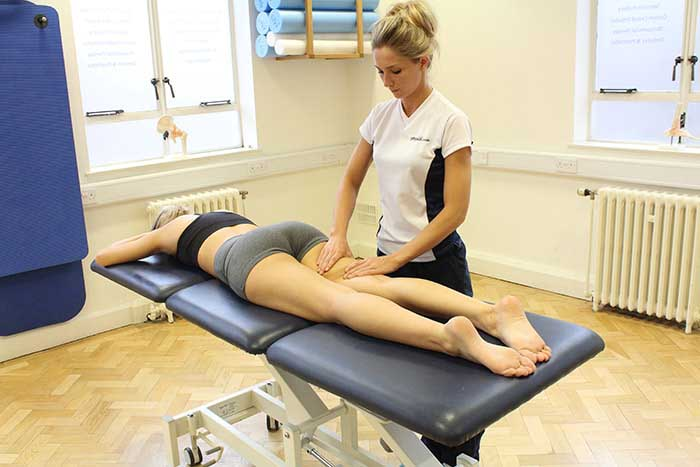 Customer receiving thigh massage while in a relaxed position in Manchester Physio Clinic