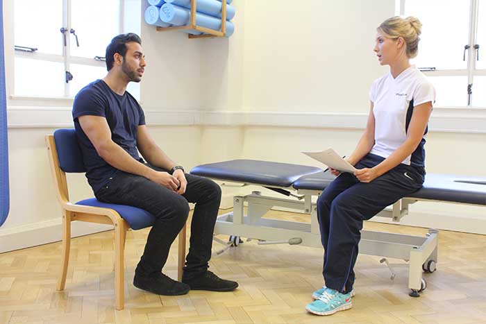 Customer having a conversation with massager in Manchester Physio Clinic