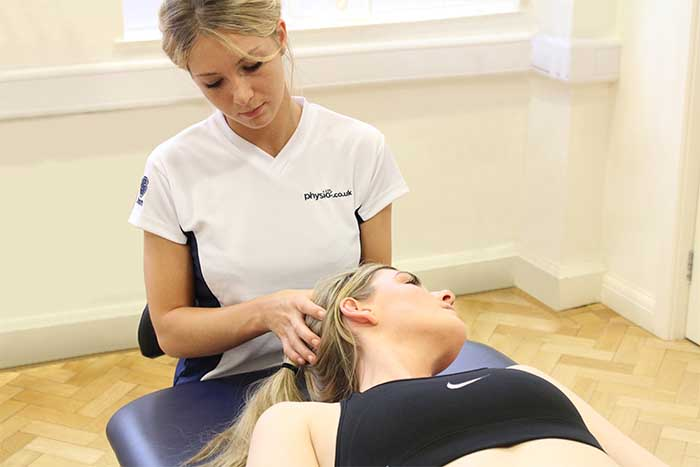 Customer receiving head massage in relaxed position in Manchester Physio Clinic
