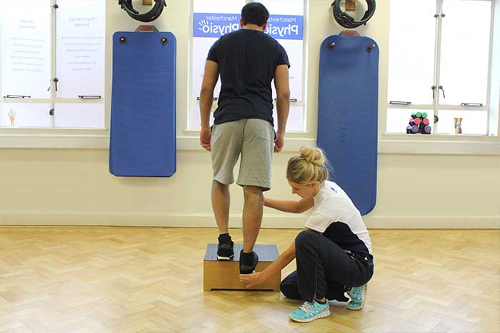 Customer receiving leg excersises with aid from instructor in Manchester Physio Clinic