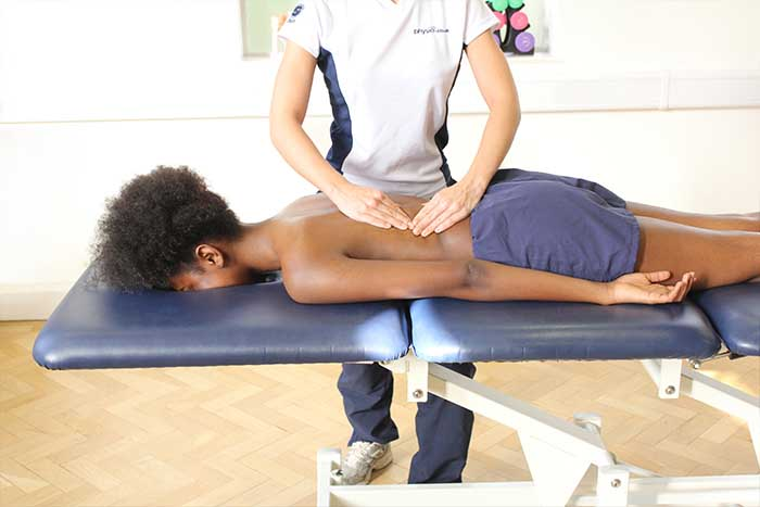 Customer reciving a lower back massage while in a relaxed position in Manchester Physio Clinic