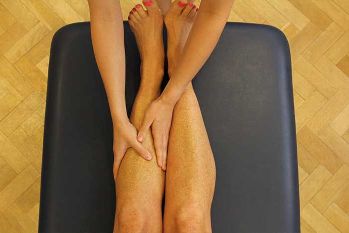 Customer receiving calf massage while in a relaxed position in Manchester Physio Clinic