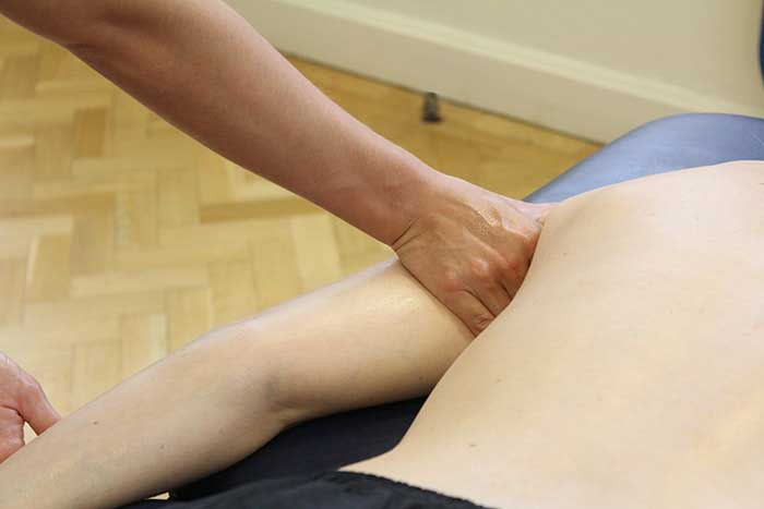 Customer receiving upper arm massage while in a relaxed position in Manchester Physio Clinic