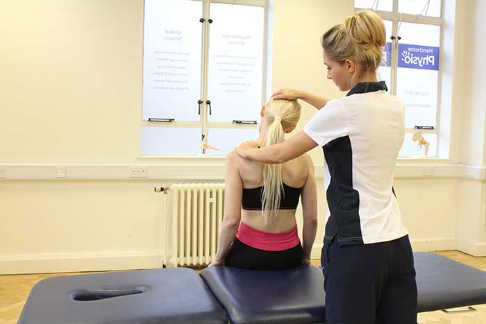 Customer receiving shoulder check in sitting up position in Manchester Physio Clinic