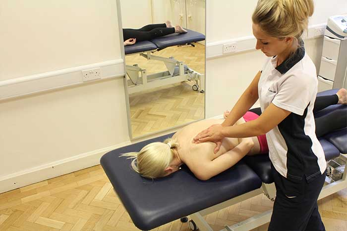 Customer receiving upper back massage in relaxed position in Manchester Physio Clinic