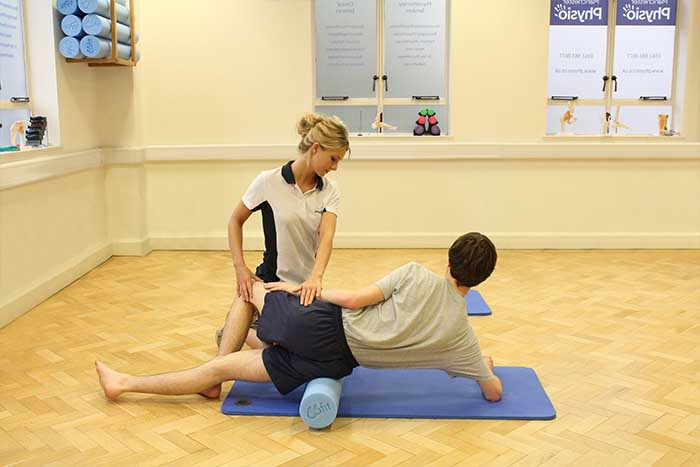 Customer receiving leg muscle stretch treatment in Manchester Physio Clinic