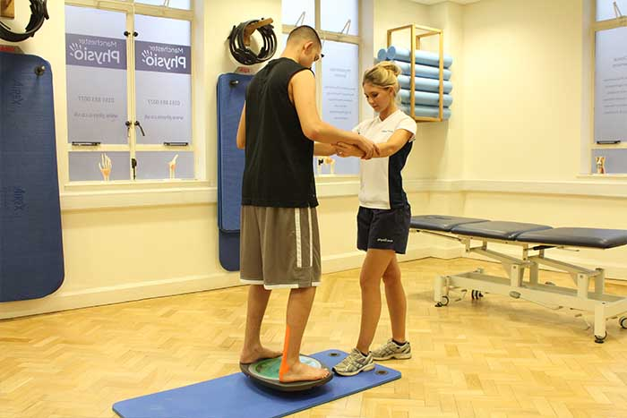 Customer receiving balance training from instructor in Manchester Physio Clinic