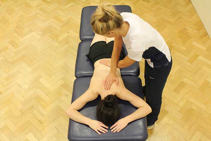 Customer receiving back massage while in a relaxed position in Manchester Physio Clinic