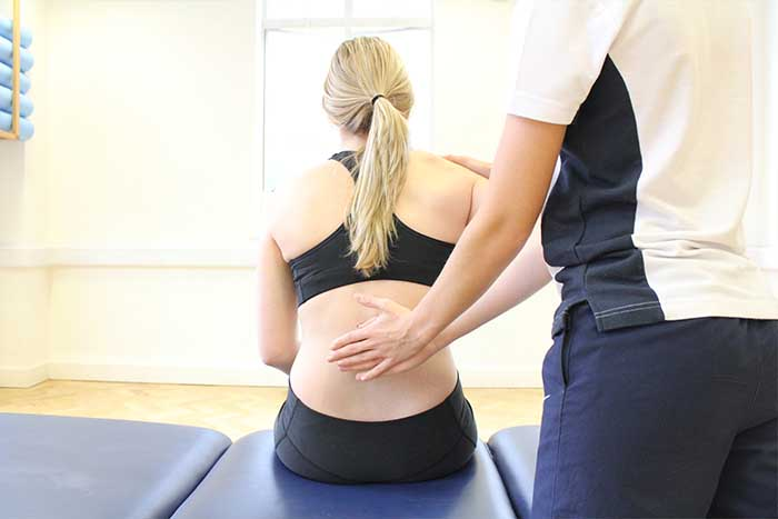 Customer receiving back support while in a sitting position in Manchester Physio Clinic