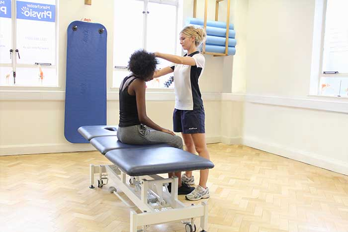 Customer receiving neck stretches aid from massager in Manchester Physio Clinic