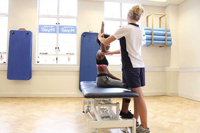 Customers arm lifted to increase strength and balance in arm in Manchester Physio Clinic