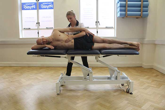 Customer receiving abdominal massage while laying on his side in Manchester Physio Clinic