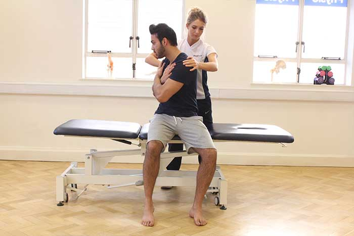 Customer reciving shoulder massage and abdominal stretches while in a sitting up position in Manchester Physio Clinic