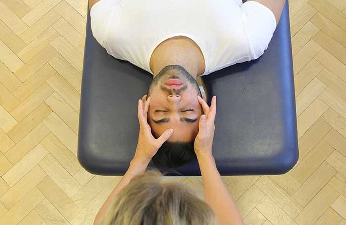 Customer receiving a head massage while in a relaxed position in Manchester Physio Clinic
