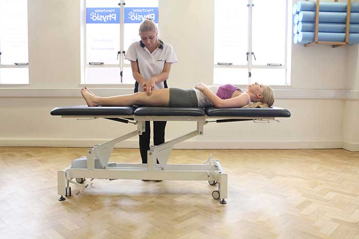 Customer reciving a thigh massage while in a relaxed position in Manchester Physio Clinic