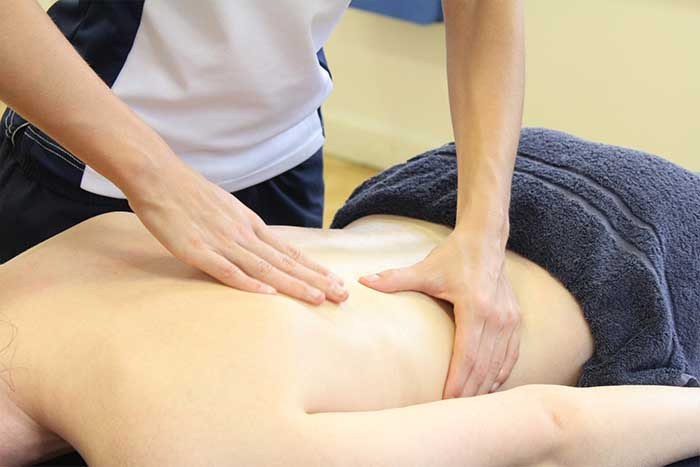 Customer reciving an upper back massage while in a relaxed position in Manchester Physio Clinic