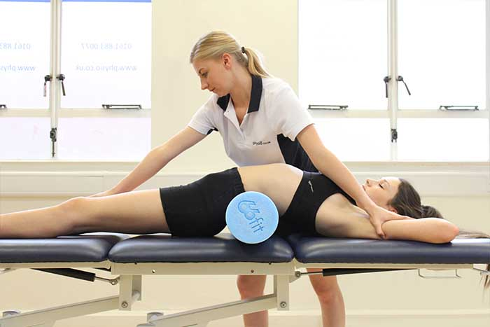 Customer receiving a back stretch while in a relaxed position in Manchester Physio Clinic