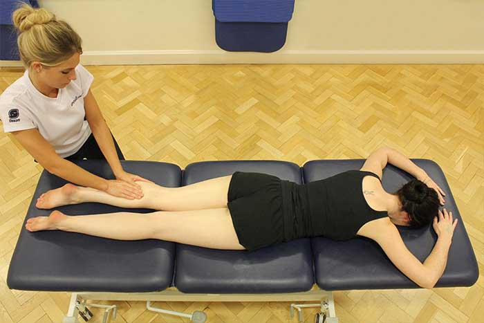 Customer receiving a calf massage while in a relaxed position in Manchester Physio Clinic