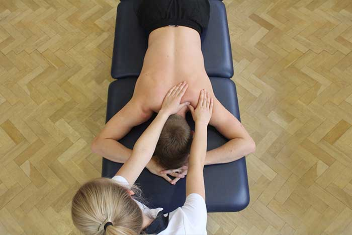 Customer receiving a shoulder massage while in a relaxed position in Manchester Physio Clinic