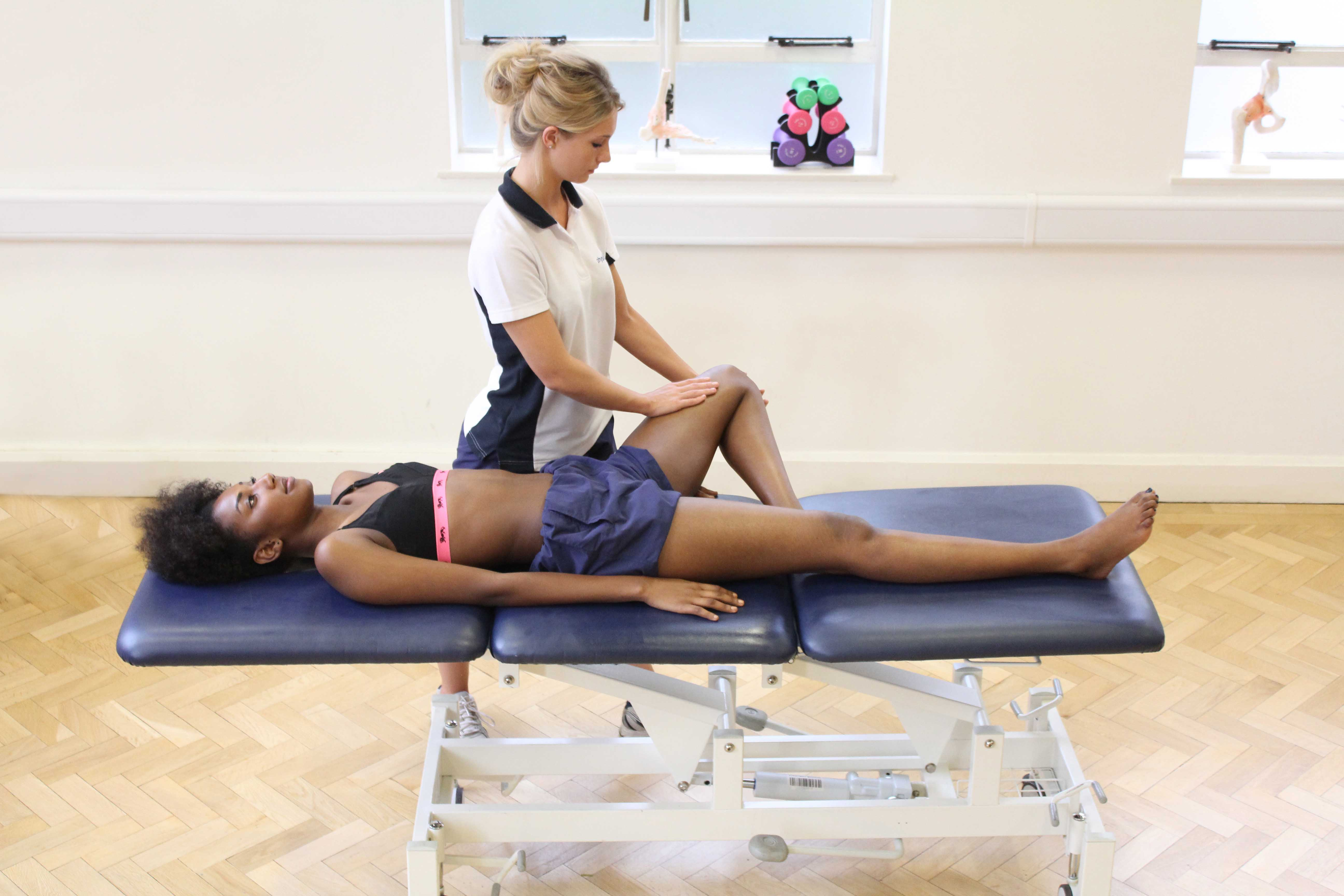 Soft tissue massage of the muscle and connective tissues around the knee
