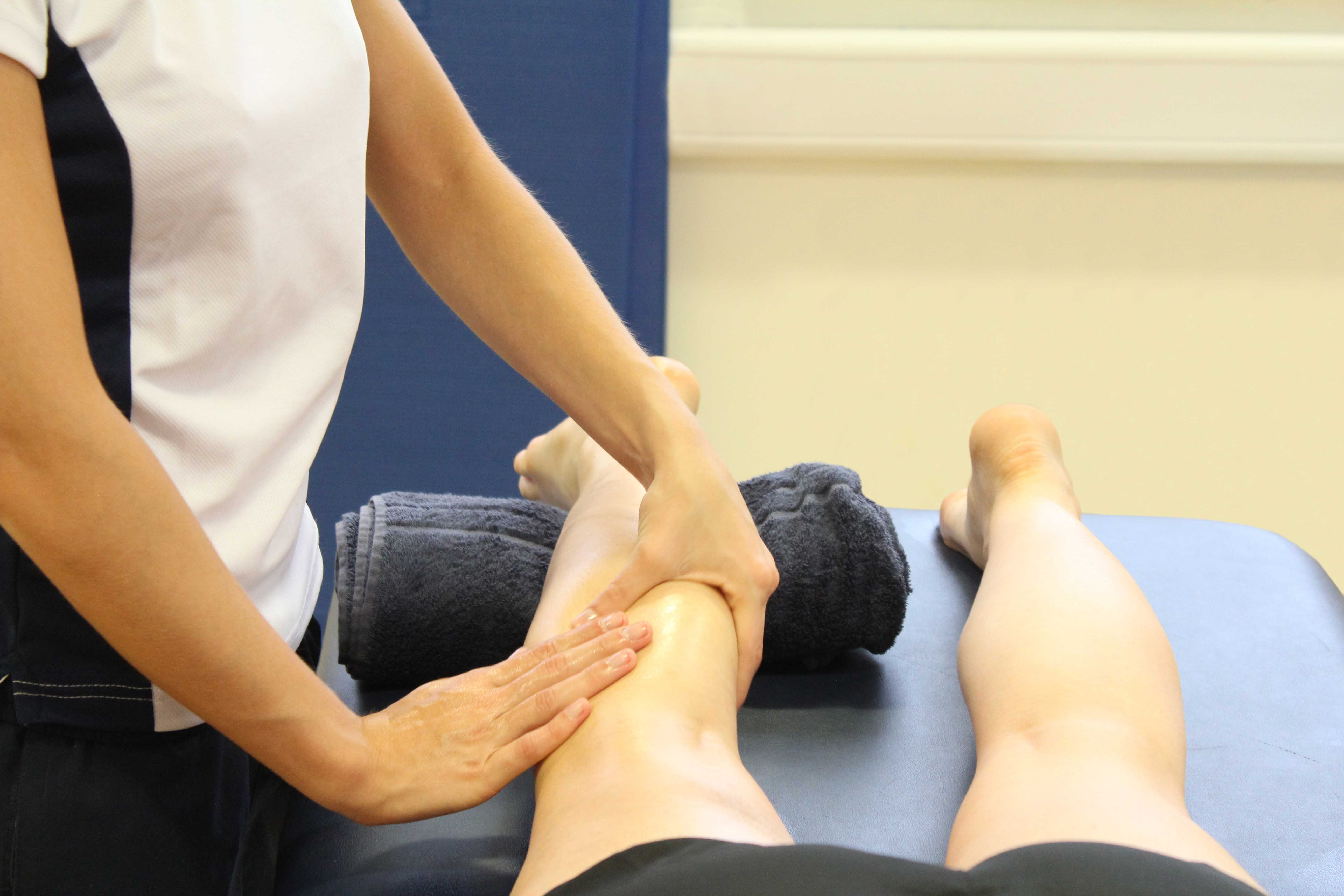 Therapist performing soft tissue massage on the tissues aound the knee