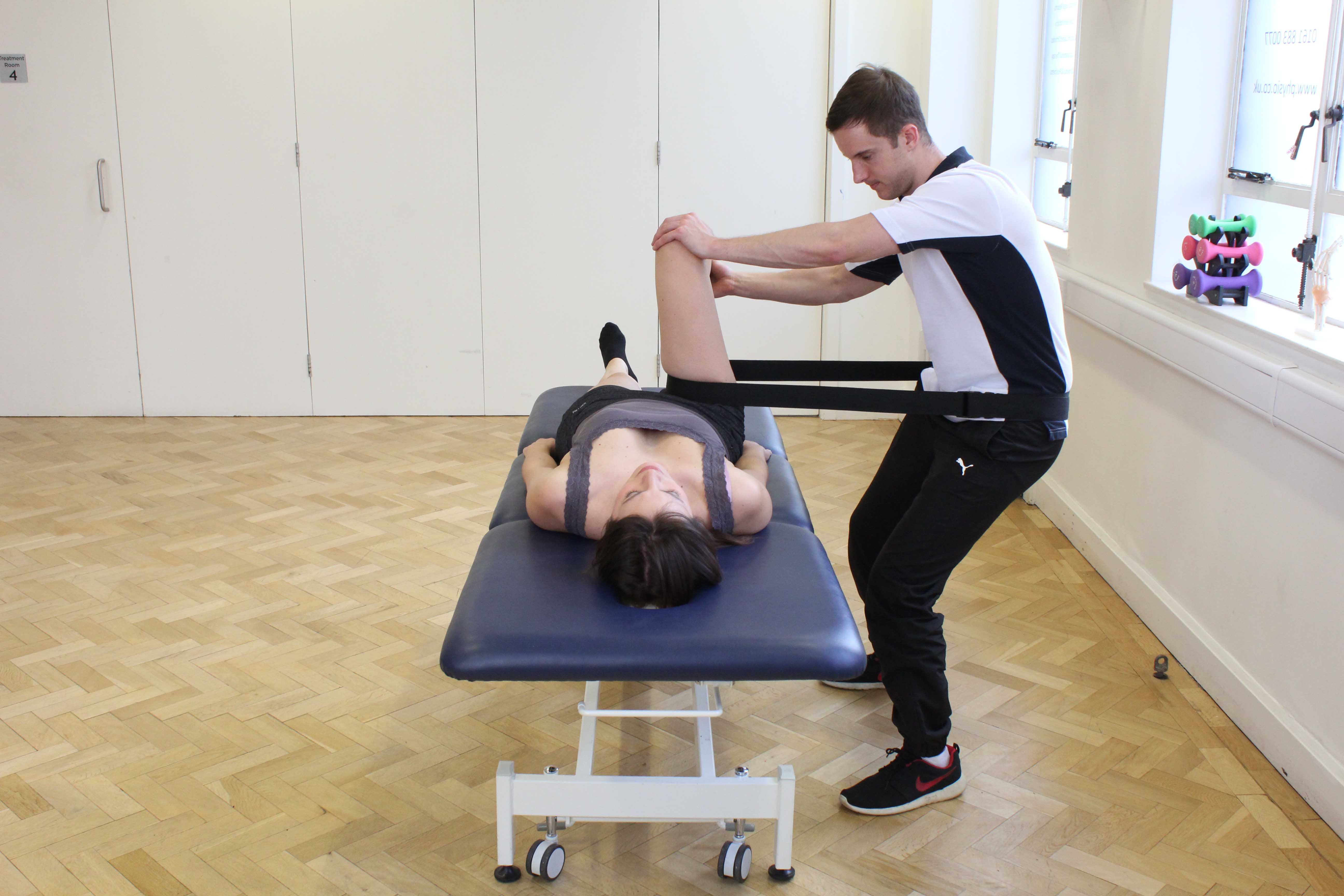 Physiotherapist using a strap to mobilise the hip joint