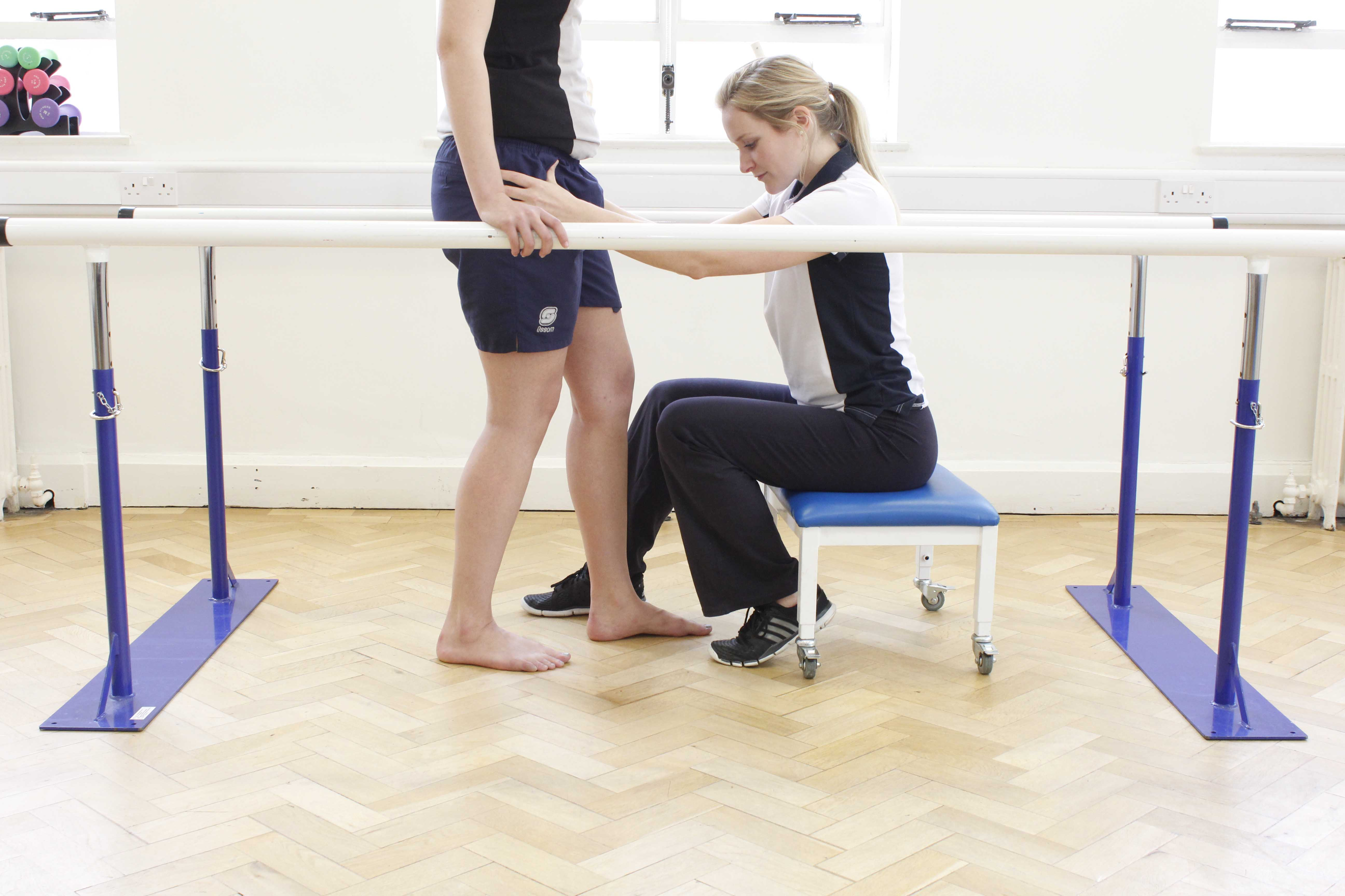 Gait re-education exercises between the parallel bars supervised by experienced physiotherapist
