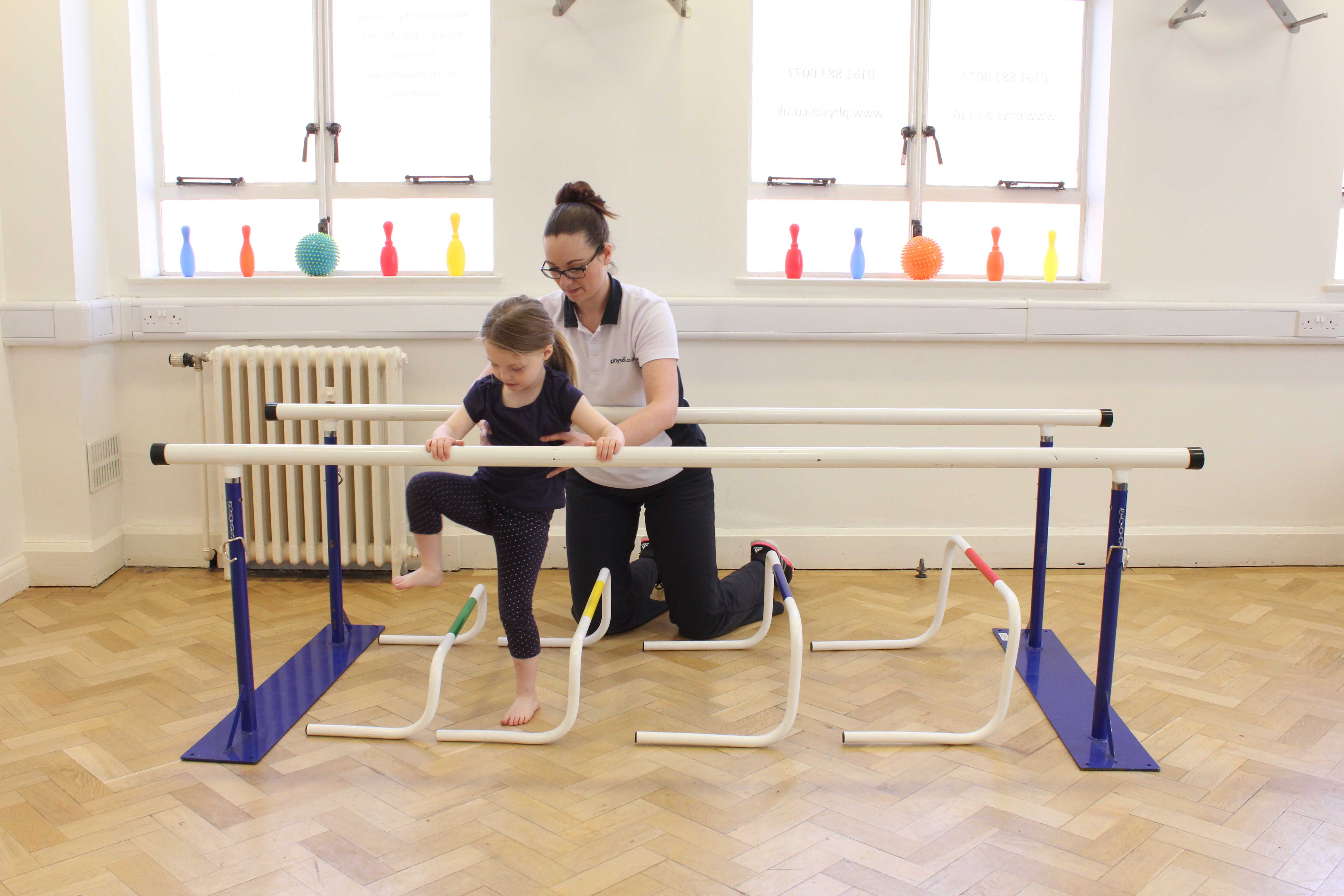 Physiotherapist assisted mobility exercises between the parallel bars