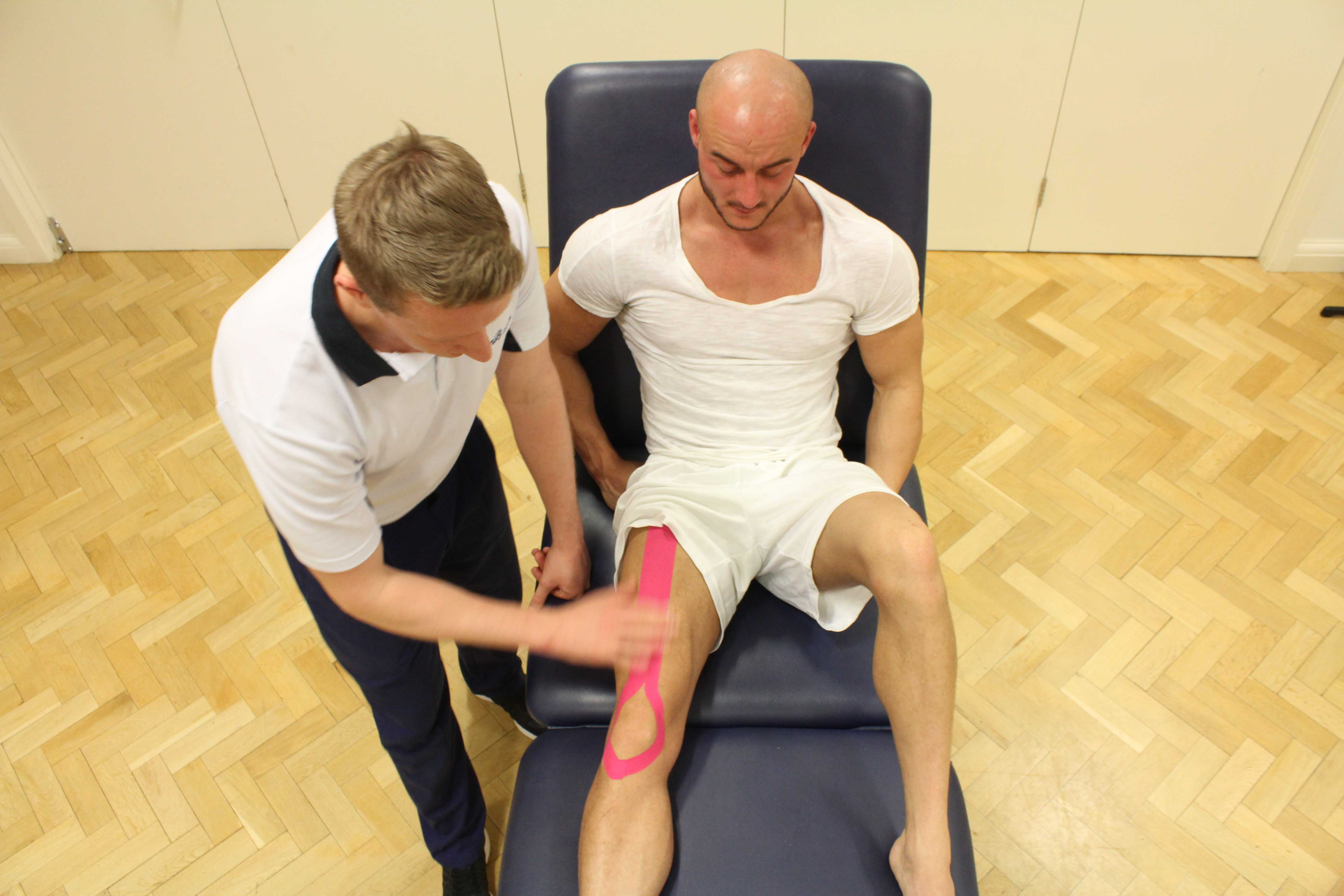 Specialist physiotherapist applying supportive tape to the knee