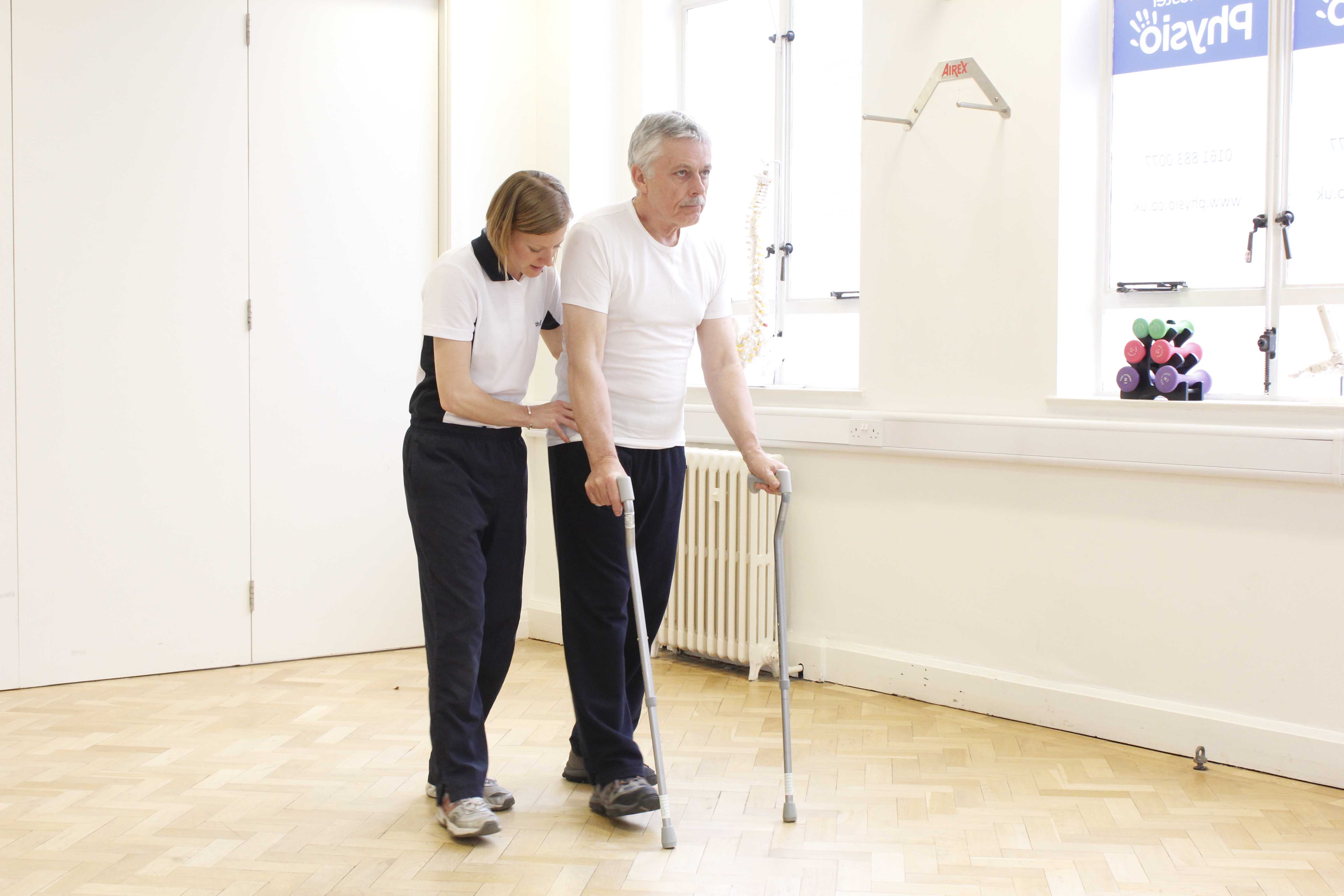 Neurological physiotherapist supervising mobility exercises using a pair of walking sticks