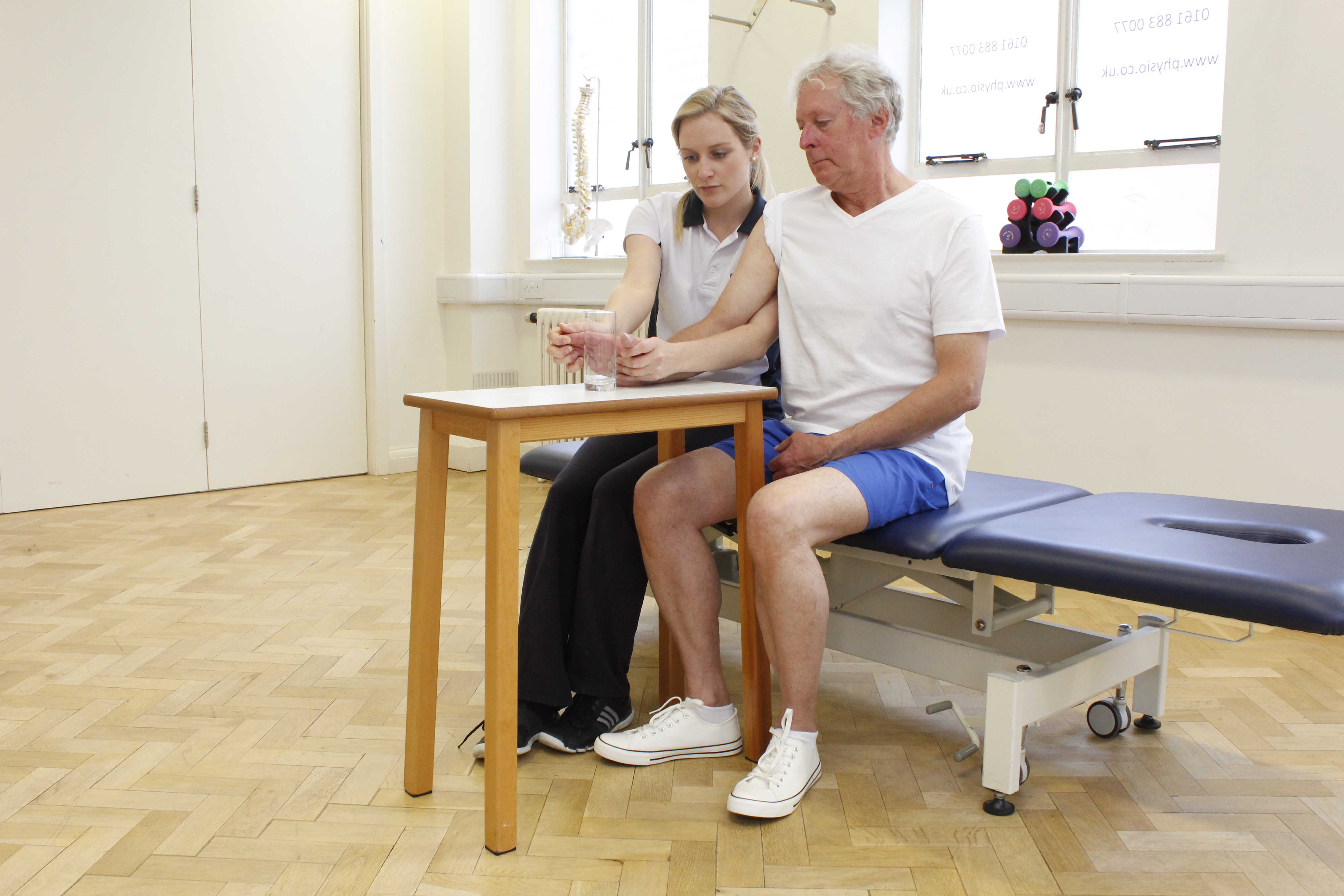 Neurological physiotherapist assisting with functional grip exercises