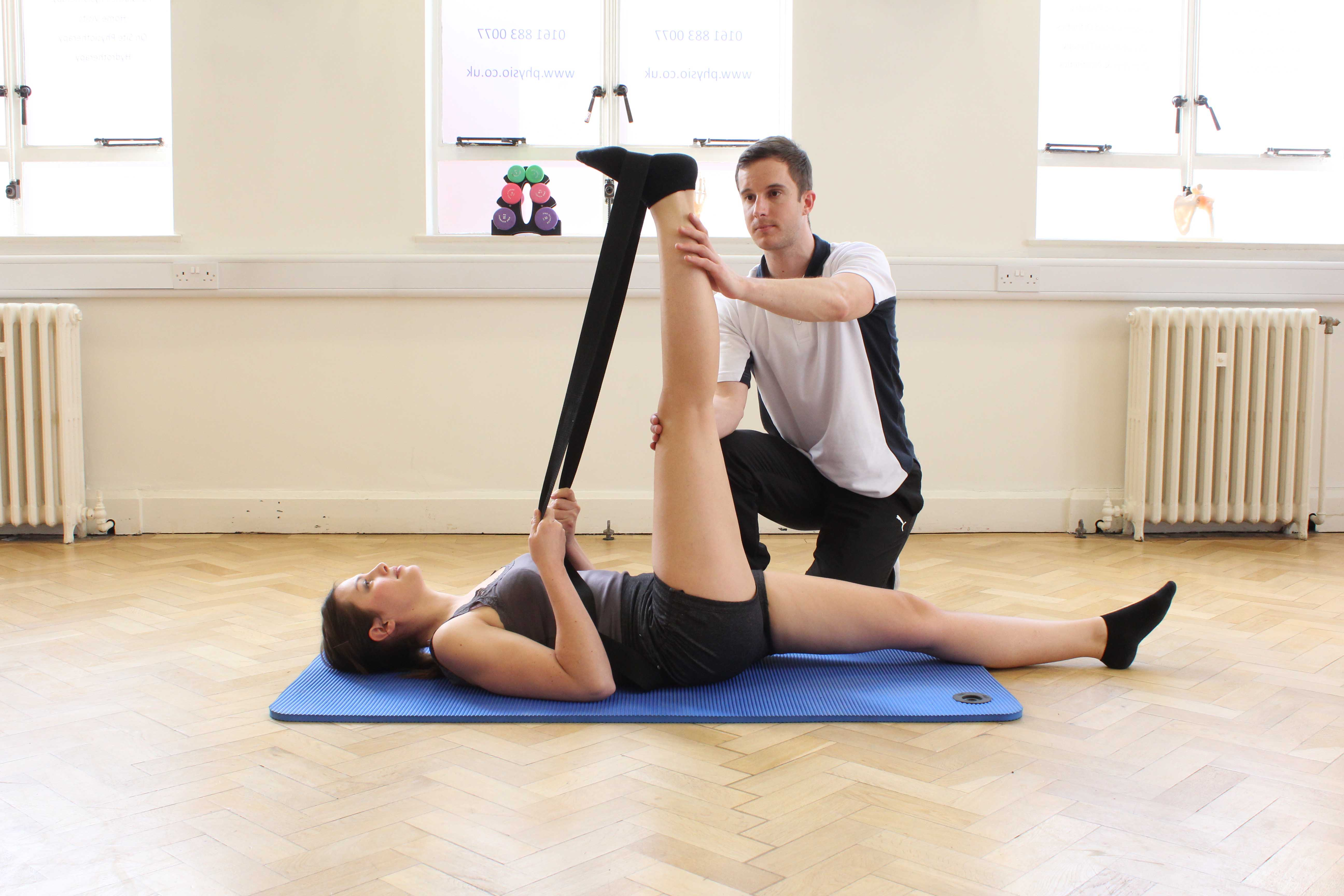 Using a resistance band under supervision of a physiotherapist to stretch the calf and hamstring muscles