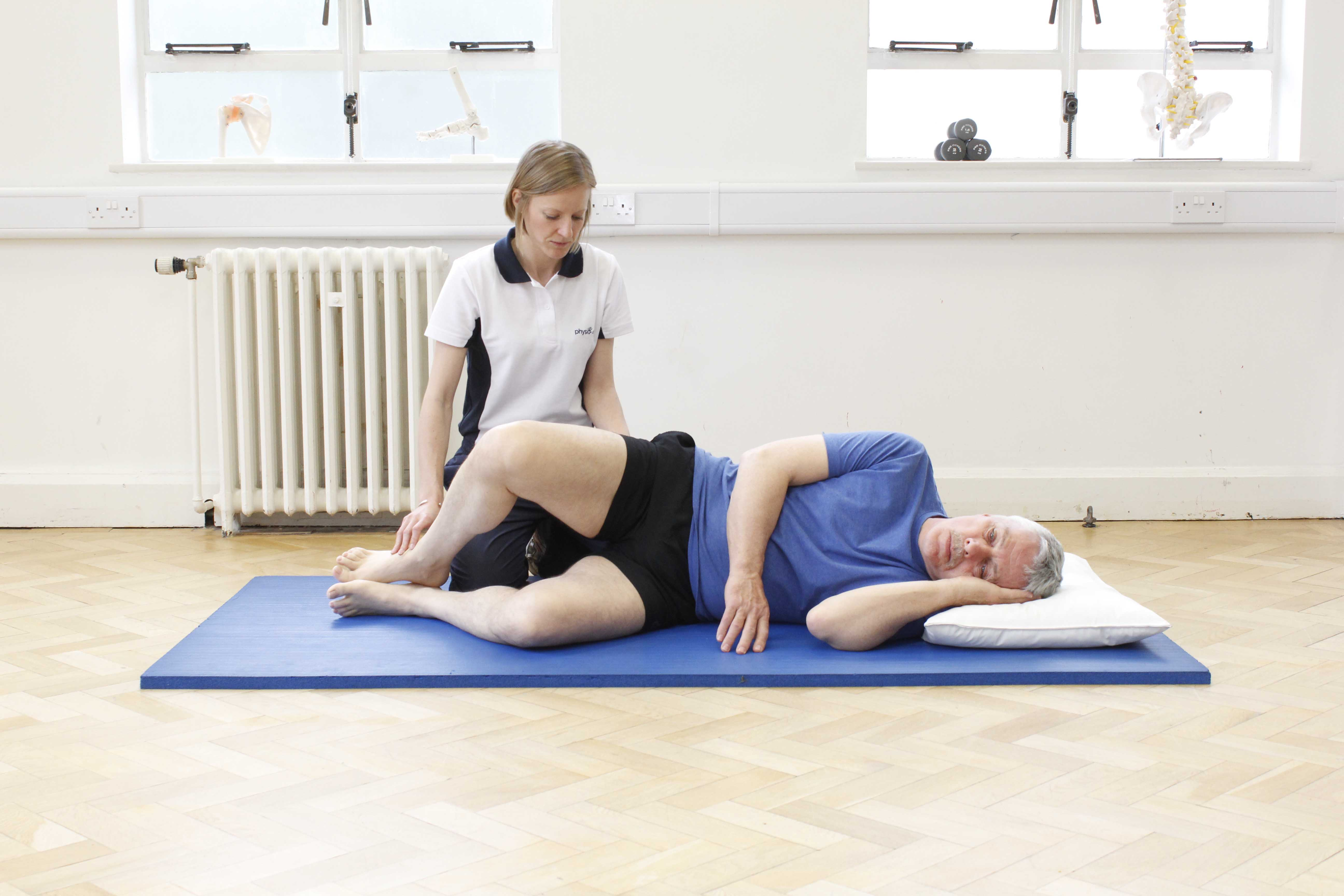 Neurological physiotherapist supervising a client performing 'Clams' to rehabilitate the hip and pelvic muscles