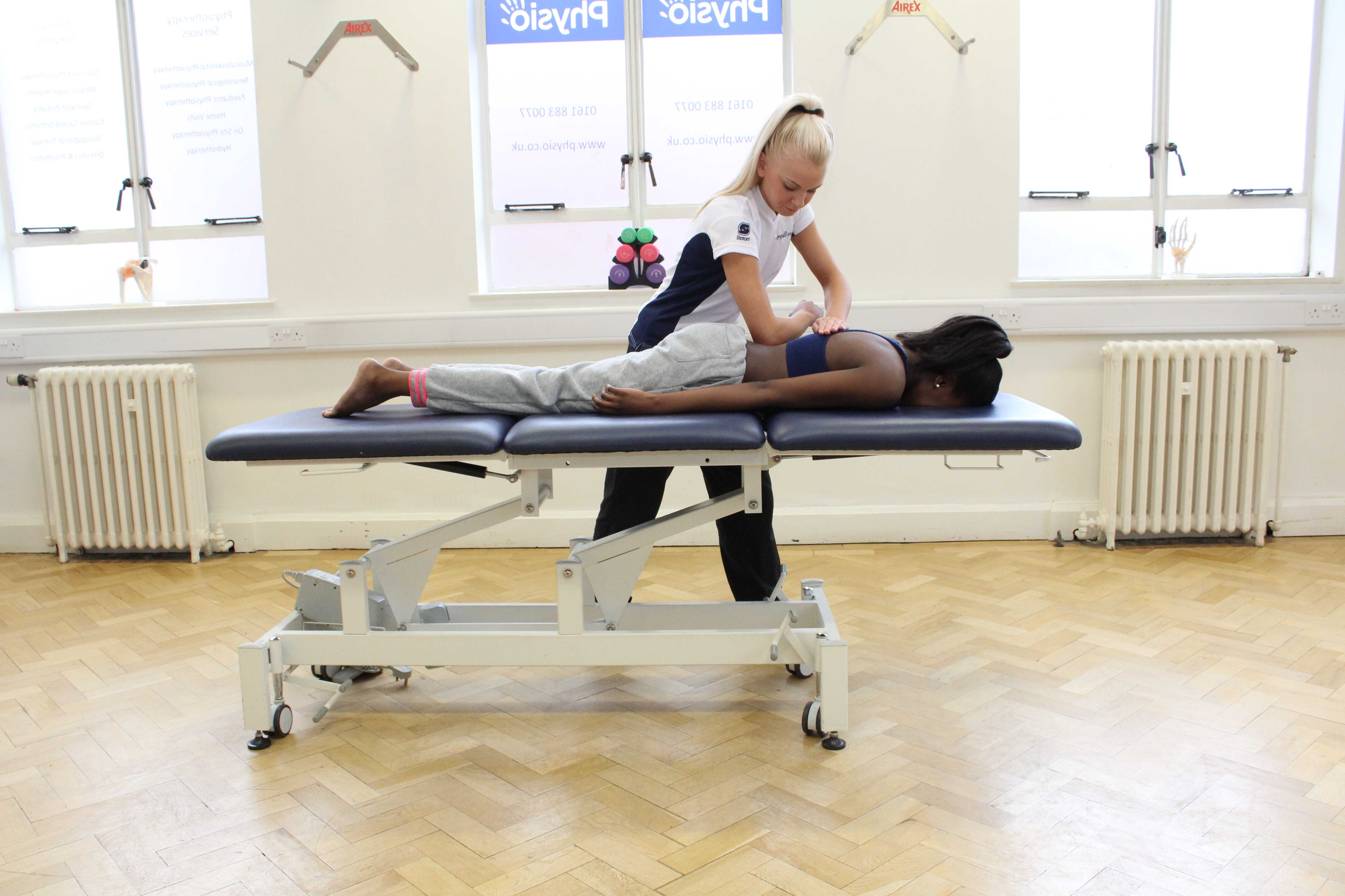 Deep tissue massage to the lumbar region by physiotherapist to lower muscle tone and aching