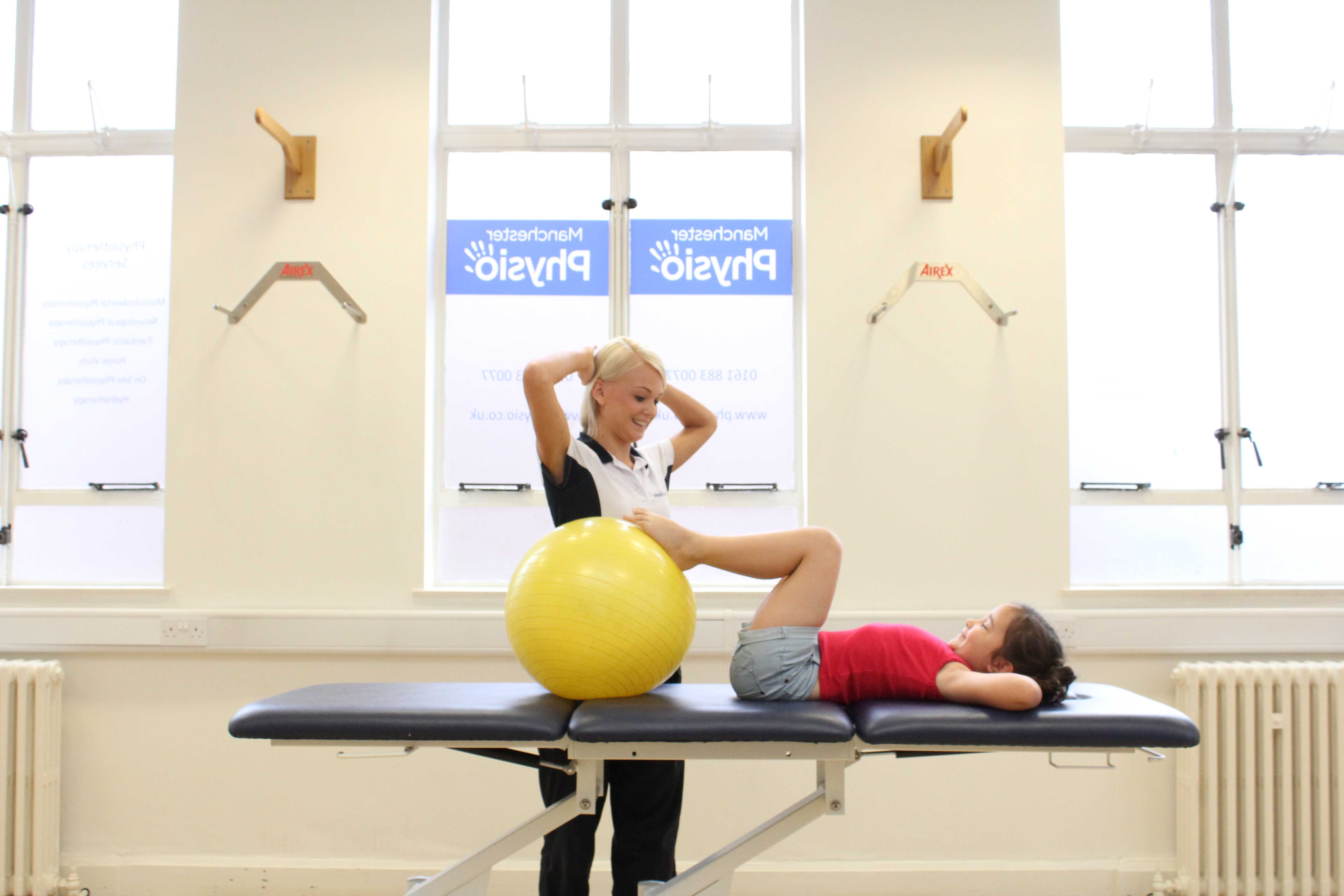 Specialist physiotherapist supervising lower limb stretching exercises using a gym ball