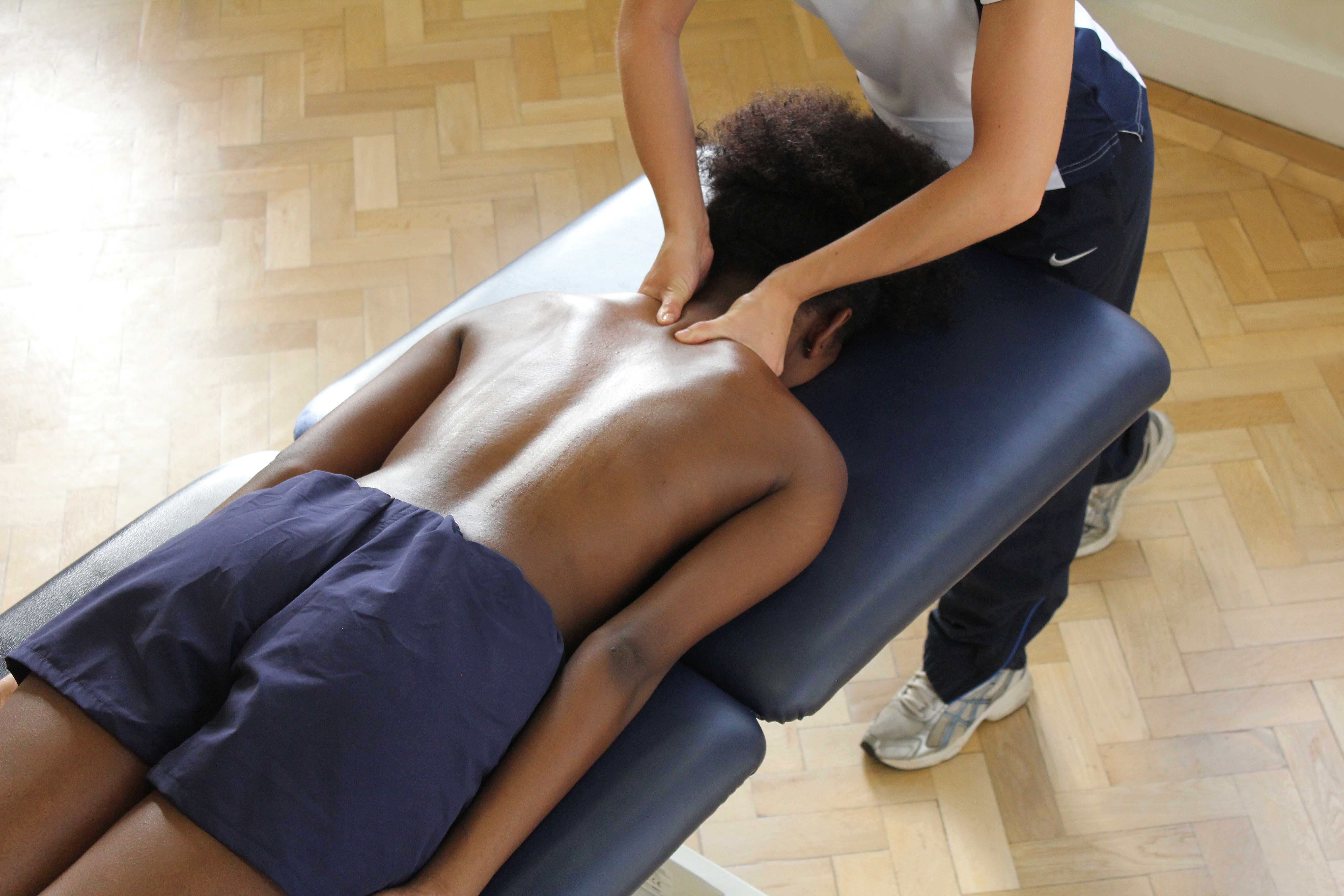 Deep tissue massage of neck focusing on the trapezius muscles