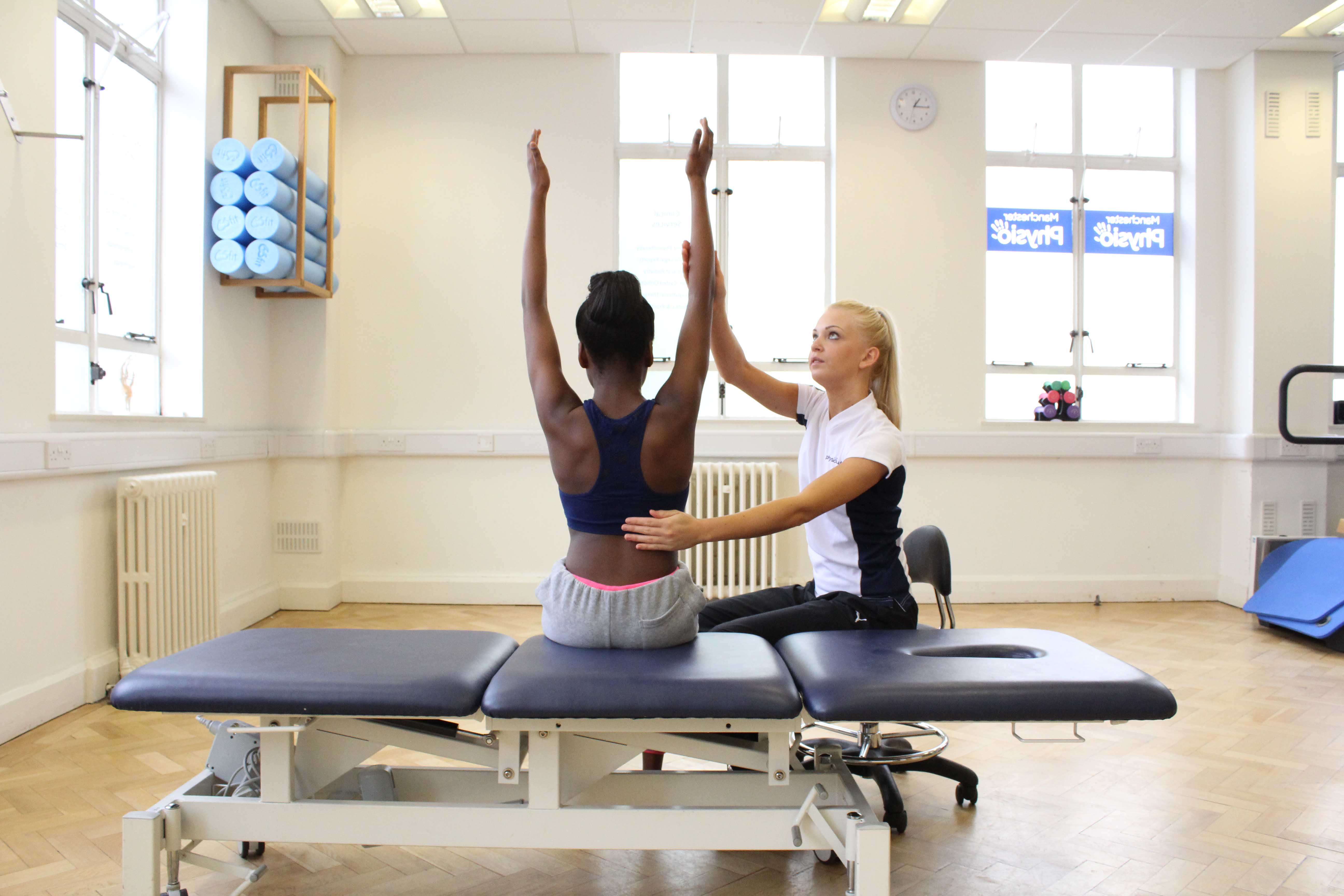Specialist physiotherapist supervising mobilisation and stretch exercises