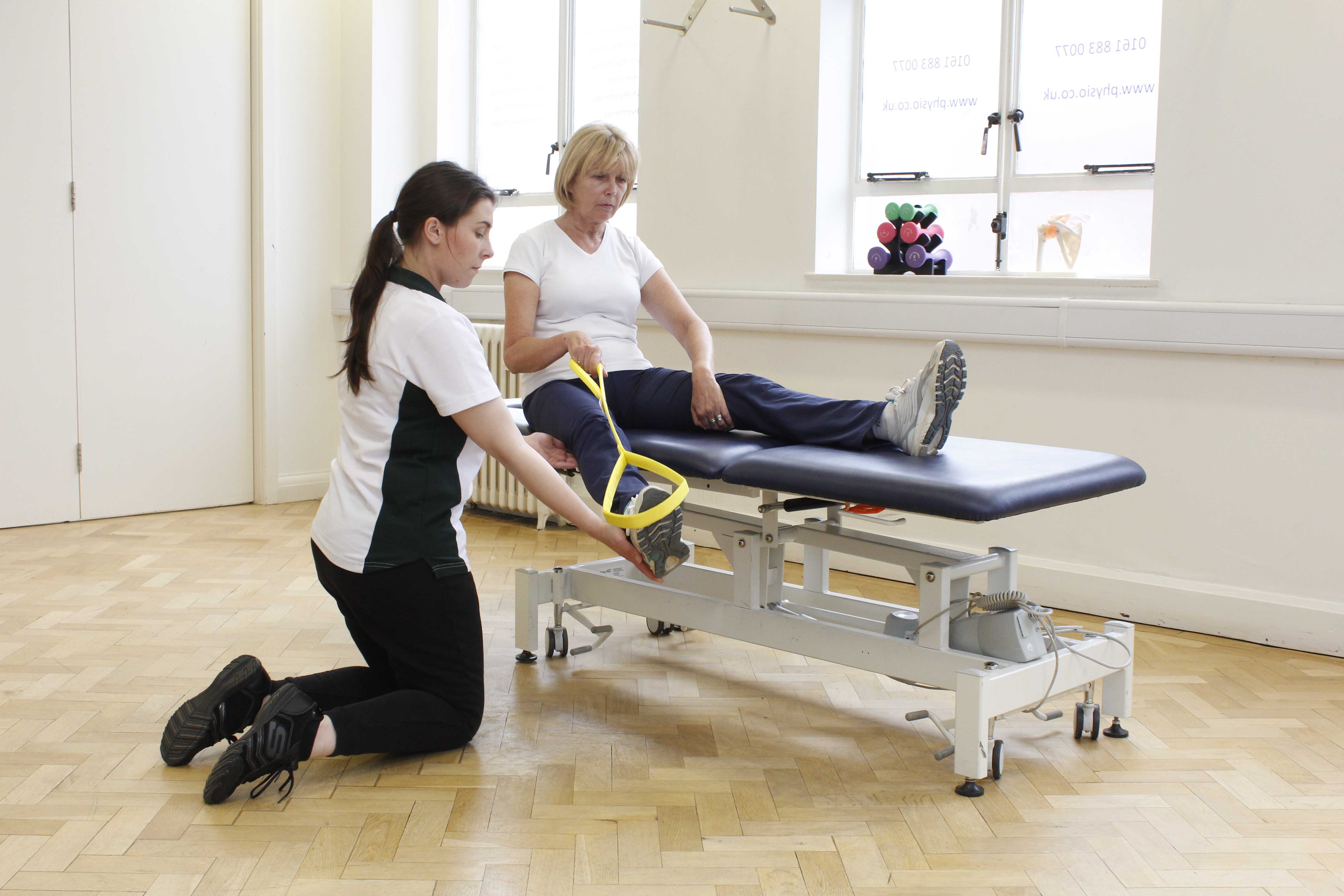 Occupational therapist assisting client with exercises to transfer in and out of bed